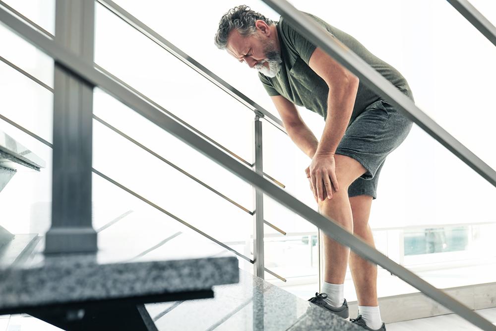 Senior mit Knieschmerz auf Treppe