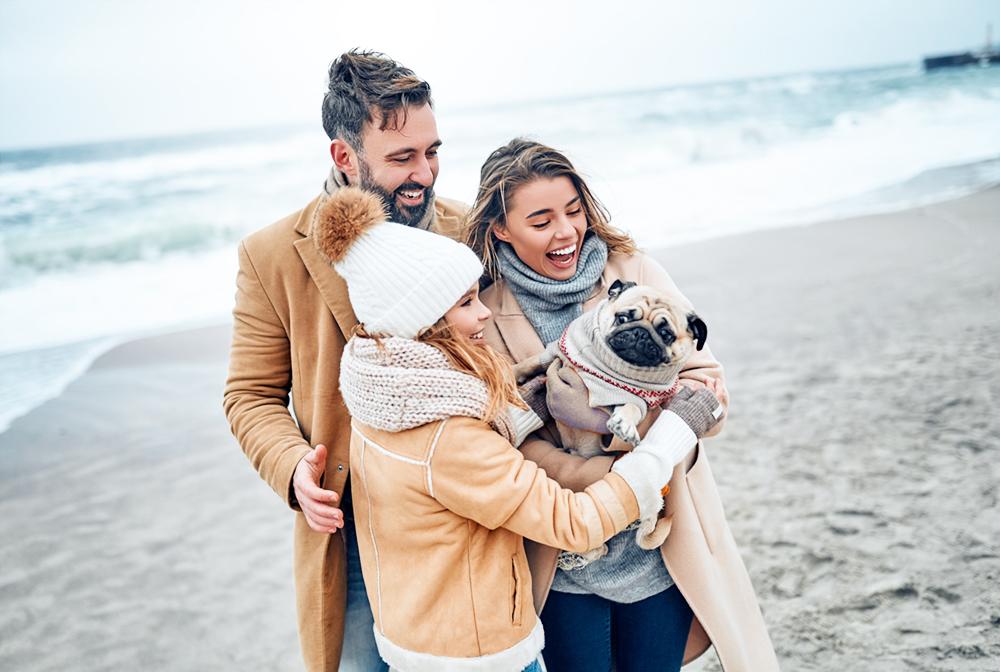 Familie am Strand mit Hund